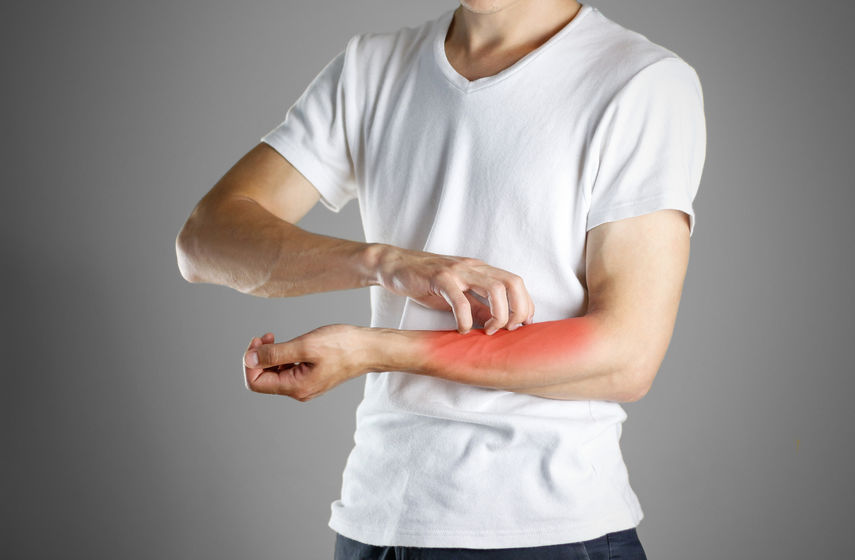 Guy in white shirt scratching his arm