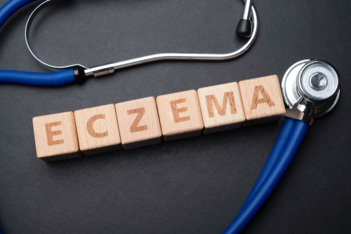 Wooden block form the word ECZEMA with stethoscope.